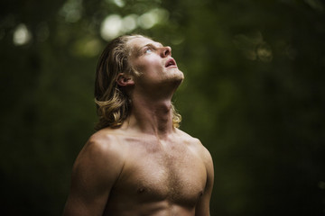 Young shirtless man looking up in forest