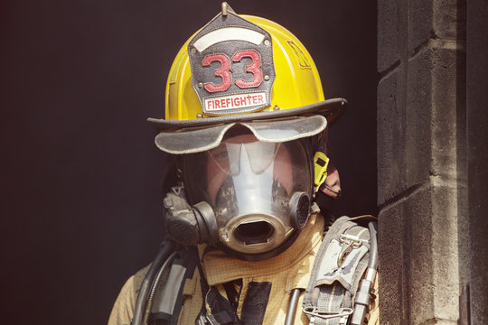 Portrait of firefighter leaning on wall