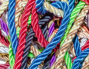 Zelfklevend Fotobehang Paradijsvogel Decorative multicolored cords of ropes scattered in a chaotic manner. Textile industry, thread, decoration