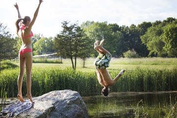 Happy woman looking at man backflipping in lake