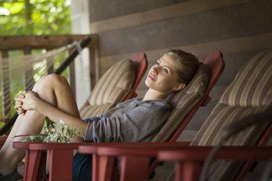 Thoughtful woman sitting on chair on patio