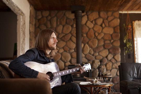 Man playing guitar in rustic living room