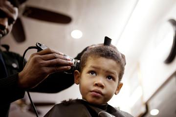 Barber giving haircut to boy at salon
