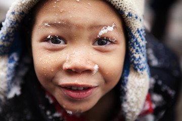 Close-up of boy face covered with snow