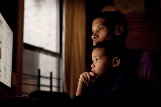 Father and son looking at computer monitor