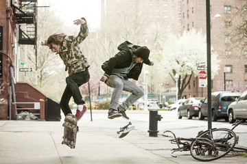Friends jumping on skateboard on sidewalk