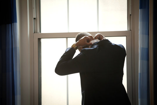 Rear view of man adjusting collar by window