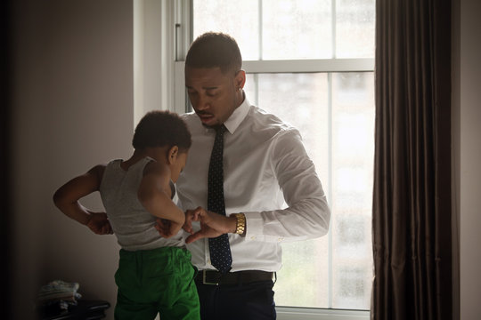 Father helping son in getting dressed