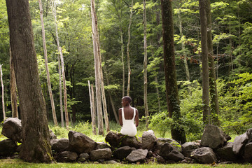 Rear view of woman sitting on rocks in forest