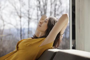 Woman in yellow dress relaxing on sofa