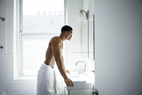 Side view of man looking in mirror in bathroom