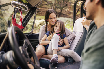 Portrait of daughter sitting with parents in off-road vehicle