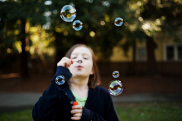 Girl blowing bubbles while standing at backyard