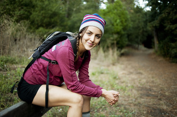 Portrait of female hiker sitting on railing in forest