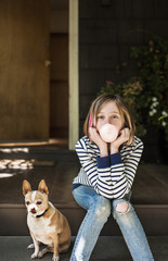 Portrait of girl blowing bubble gum while sitting with dog on porch