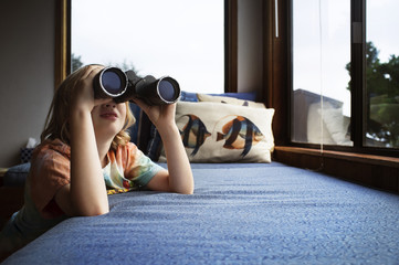 Boy using binoculars at home