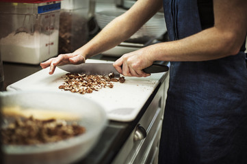 Woman cutting pecans in commercial kitchen