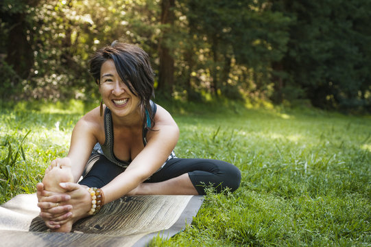 Portrait of woman exercising on grassy field