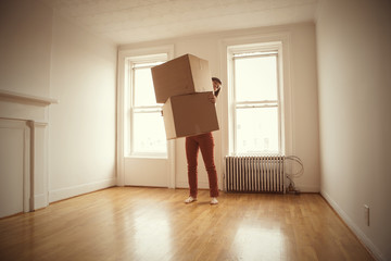 Woman carrying boxes while standing at home