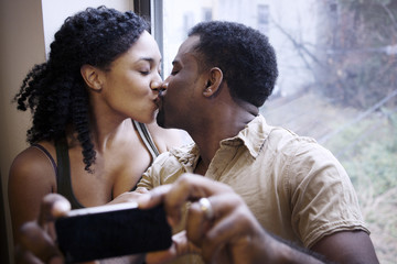 Couple taking selfie while kissing against window