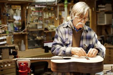 Man adjusting guitar strings at workshop