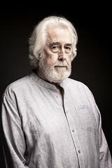 Portrait of senior man with white hair against black background
