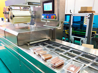 Plastic containers with sausages on conveyor at food factory