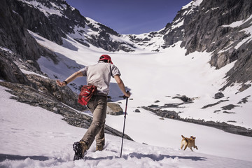 Rear view of man with dog climbing snow covered mountain