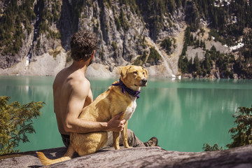 Side view of man sitting with Labrador Retriever against lake