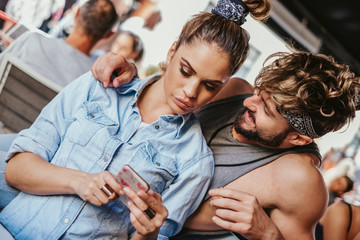 Disappointed girlfriend showing mobile phone to her boyfriend