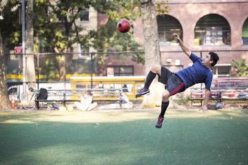 Soccer player kicking ball at field
