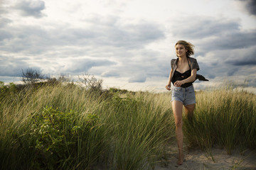 Smiling woman running on grassy field against cloudy sky