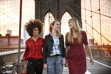 Smiling friends talking while standing on Brooklyn Bridge