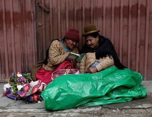 Aymara women read a book near a market in La Paz