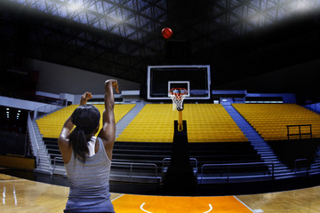 Rear view of woman practicing basketball in court