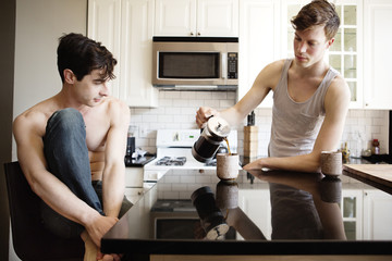 Gay man looking at boyfriend pouring coffee in cup