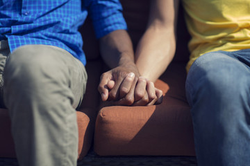 Midsection of gay couple holding hands while sitting on sofa in lawn