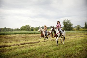 Cowgirls horseback riding on field against sky