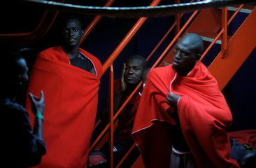 """Migrants are seen on the """"Mastelero"""" rescue vessel as they wait to disembark after arriving at the port of Malaga"""