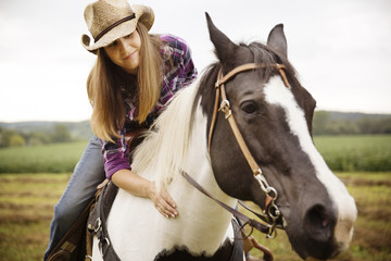 Woman stroking horse while riding