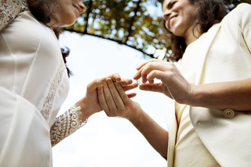Woman puts ring on wife's finger during wedding ceremony