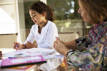 Grandmother looking at granddaughter studying by table