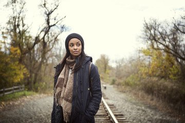 Woman with hands in pockets looking away while standing on railroad track