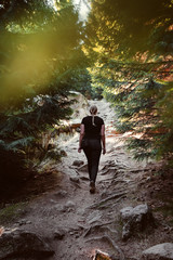 Back view of a blonde girl hiking in a dark moody mountain path in a mysterious nature pine forest. Brocken, nature reserve Harz mountains, National Park Harz in Saxony-Anhalt, Germany