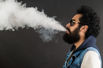 Young man vaping, studio shot. Bearded guy with sunglasses blowing a cloud of smoke on black background. Concept of smoking and steam without nicotine, copy space