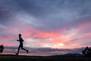 Athlete running in field at sunset