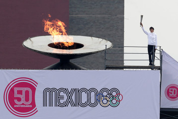 Enriqueta Basilio holds the Olympic torch beside the cauldron at the University Olympic Stadium to mark the 50th Anniversary of the 1968 Olympic Games, in Mexico City
