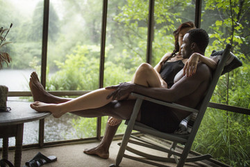 Affectionate couple sitting on rocking chair in cottage