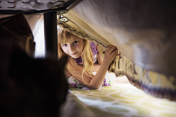 Girl looking at cat through blanket under bed