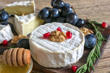 camembert cheese with grapes, pomegranate seeds, honey walnuts and rosemary on wooden cutting board.